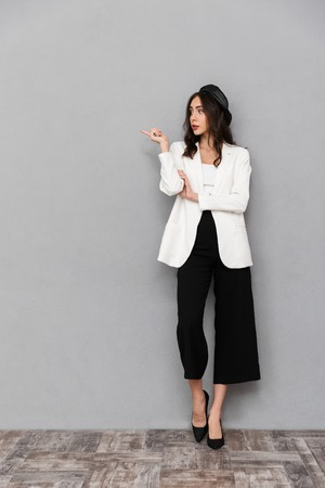 Full length portrait of a pretty young woman dressed in jacket and pants standing over gray background, pointing away
