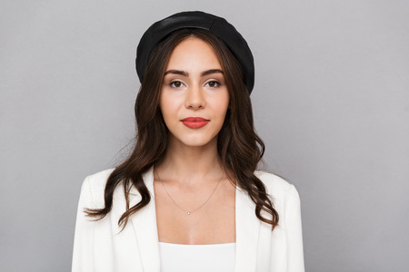 918620f1f70 Portrait of a beautiful young woman wearing beret standing isolated over  gray background