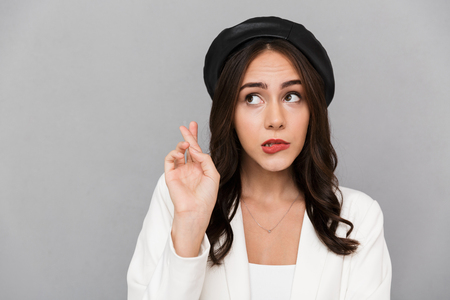 Portrait of a worried young woman wearing beret standing isolated over gray background, holding fingers crossed for good luck Banco de Imagens