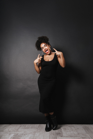 Full length photo of pretty african american woman wearing black dress gesturing isolated over dark background Stock fotó