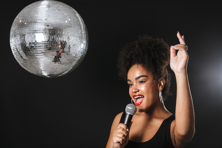 Beautiful african woman standing with silver disco ball isolated over black background, holding microphone, singing