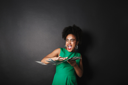 Portrait of a happy afro american woman wearing dress standing over black wall, throwing paper money away