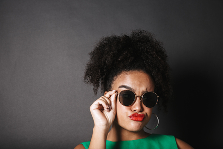 Portrait of a beautiful afro american woman wearing sunglasses standing isolated over black background, posing Stock Photo
