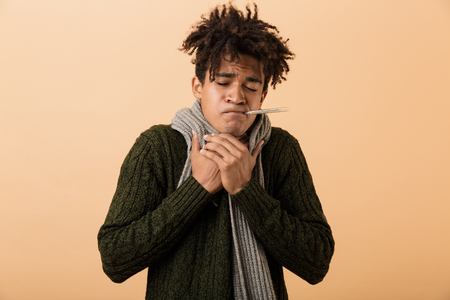 Portrait of frozen african american guy wearing sweater and scarf grabbing throat with thermometer in his mouth isolated over beige background 版權商用圖片