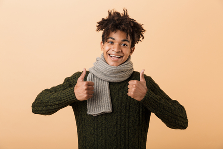 Portrait of cheerful african american guy wearing sweater and scarf showing thumbs up isolated over beige background