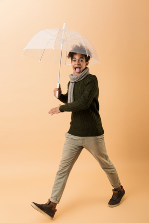 Full length photo of teen african american guy wearing sweater and scarf walking under umbrella isolated over beige background