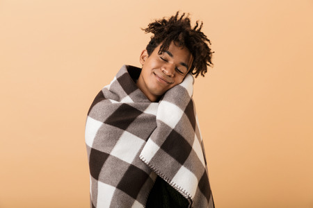 Portrait of cheerful african american boy smiling while covering in blanket isolated over beige background