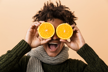 Portrait of joyful african american guy wearing sweater and scarf covering eyes with two pieces of orange isolated over beige background Banco de Imagens