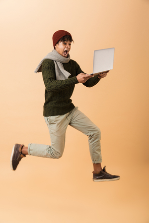 Full length photo of excited african american guy wearing hat and scarf walking with laptop isolated over beige background