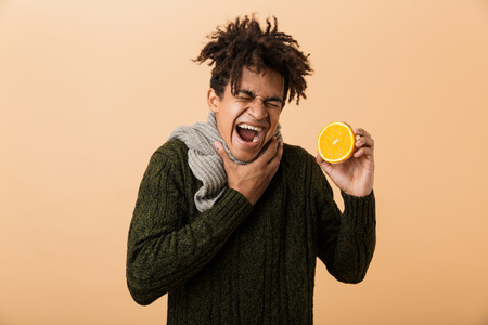 Portrait of sick african american guy wearing sweater and scarf touching throat and holding half an orange isolated over beige background 스톡 콘텐츠
