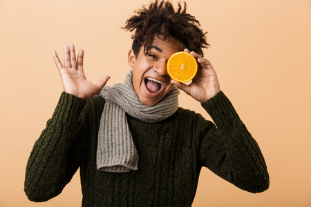 Portrait of cheerful african american boy wearing sweater and scarf holding half an orange isolated over beige background