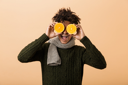 Portrait of funny african american guy wearing sweater and scarf covering eyes with two pieces of orange isolated over beige background 免版税图像