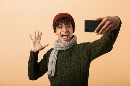 Portrait of a happy young african man dressed in autumn clothes isolated over beige background, taking a selfie Imagens - 114482006