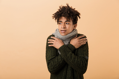 Portrait of frowning african american guy wearing sweater and scarf trembling due to cold isolated over beige background Stock Photo - 114482012