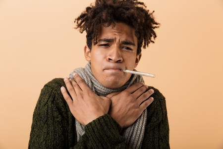 Portrait of sad african american guy wearing sweater and scarf grabbing throat with thermometer in his mouth isolated over beige background 스톡 콘텐츠