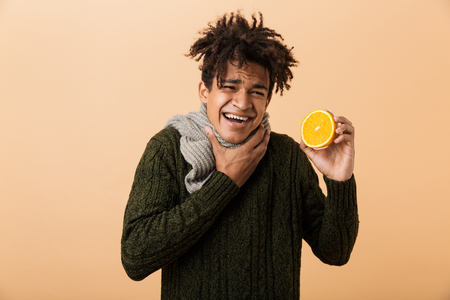 Portrait of unhappy african american guy wearing sweater and scarf touching throat and holding half an orange isolated over beige background Stock Photo