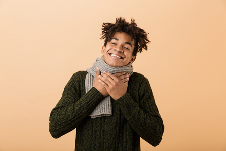 Portrait of happy african american man wearing sweater and scarf touching throat isolated over beige background