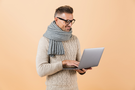 Portrait if a happy man dressed in sweater and scarf standing isolated over beige background, working on laptop computer