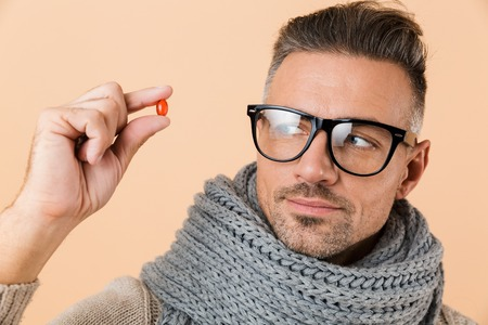 Close up portrait of a serious pensive man dressed in sweater and scarf standing isolated over beige background, showing pill capsule