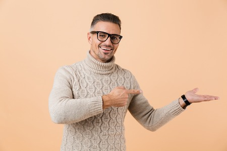Portrait of a happy man dressed in sweater standing isolated over beige background, pointing away at copy space on his palm
