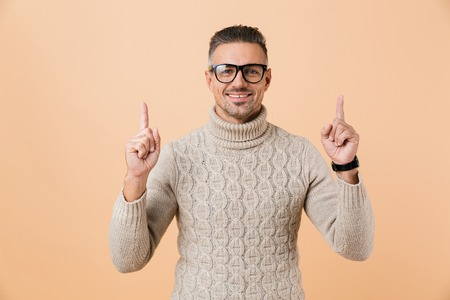 Portrait of an excited man dressed in sweater standing isolated over beige background, pointing up Imagens