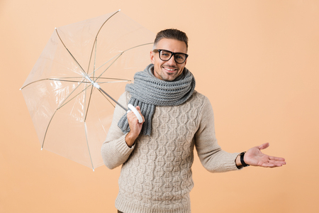 Portrait of a cheerful man dressed in sweater and scarf standing under umbrella isolated over beige background Standard-Bild - 113859467
