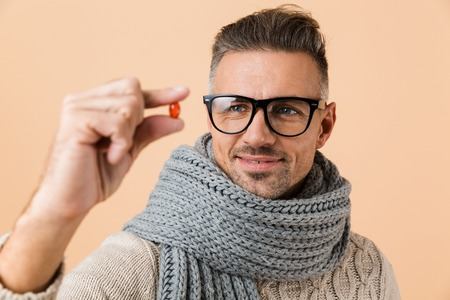 Close up portrait of a smiling man dressed in sweater and scarf standing isolated over beige background, showing pill capsule Stock Photo