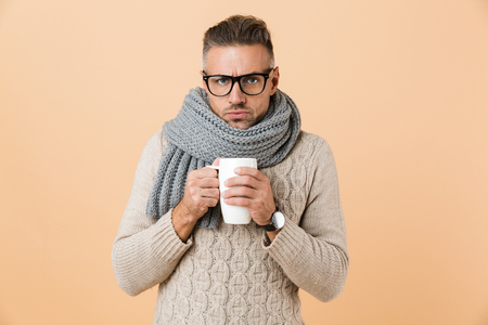 Portrait if a frozen man in eyeglasses dressed in sweater and scarf holding cup of hot tea isolated over beige background