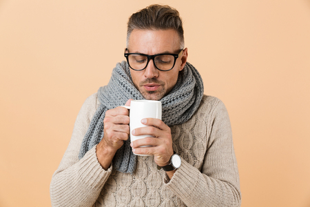 Portrait if a frozen man dressed in sweater and scarf holding cup of hot tea isolated over beige background 스톡 콘텐츠