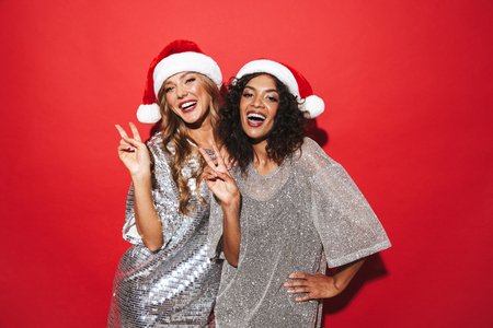 Two cheerful young smartly dressed women celebrating New Year isolated over red background, posing