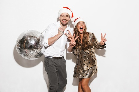 Cheerful young smartly dressed couple celebrating New Year party isolated over white background, dancing Stockfoto