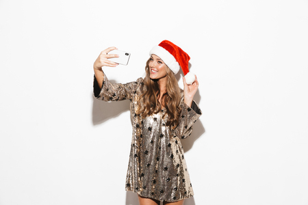 Portrait of a pretty young woman wearing red hat celebrating New Year isolated over white background, taking a selfie with mobile phone Stock Photo