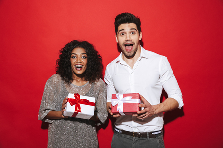 Cheerful smartly dressed couple standing isolated over red background, celebrating New Year, holding presents