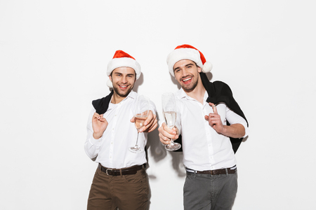 Two cheerful smartly dressed men standing isolated over white background, celebrating New Year, drinking champagne