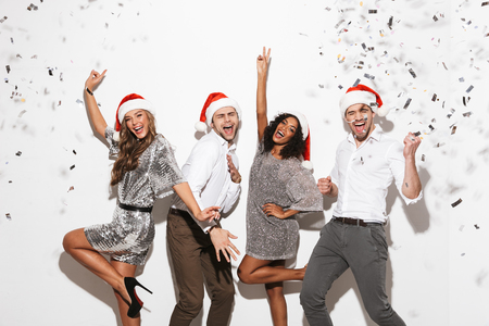 Group of cheerful smartly dressed friends celebrating New Year isolated over white background, dancing