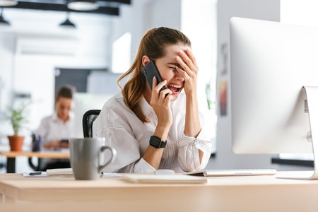 Shocked disappointed young businesswoman dressed in shirt sitting at her workplace at the office, talking on mobile phone
