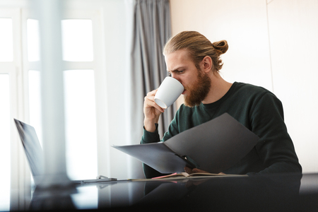 Busy young man working on laptop computer at home, sitting at the kitchen, drinking tea