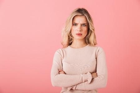 Porträt einer verärgerten jungen Frau, die einen Pullover trägt, der isoliert auf rosa Hintergrund steht, die Arme verschränkt Standard-Bild