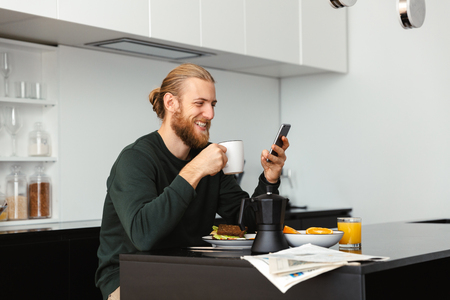 Handsome young man having breakfast, reading newspaper while sitting at the kitchen, using mobile phone Stok Fotoğraf