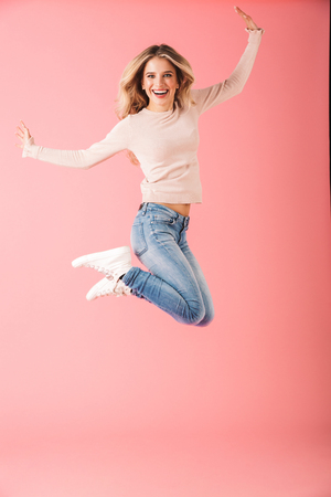 Full length portrait of a happy young woman wearing sweater jump isolated over pink background