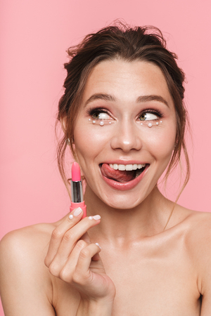 Image of a pretty happy young woman posing isolated over pink wall background holding lipstick.