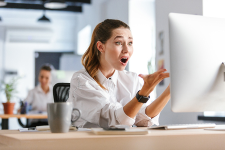 Shocked young businesswoman sitting at her workplace at the office, looking at computer