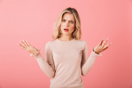 Portrait of an upset young woman wearing sweater standing isolated over pink background, shrugging shoulders
