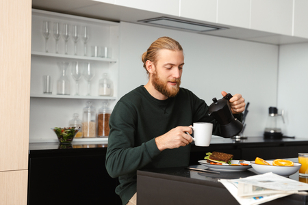 Handsome young man having breakfast, reading newspaper while sitting at the kitchen