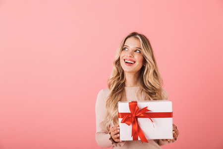 Portrait of a lovely blonde haired young woman standing isolated over pink background, holding gift box