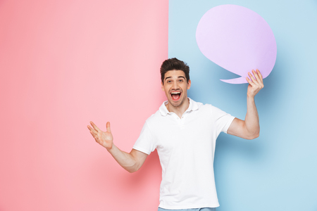 Excited young man standing isolated over two colored background, holding empty speech bubble