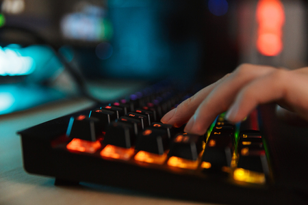Close up of a woman's hand typing on a gamer keyboard