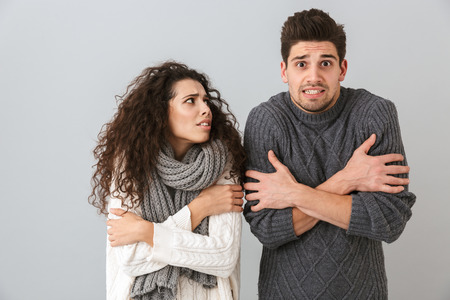 Photo of frozen couple man and woman wearing scarfs trembling and hugging themselves isolated over gray background