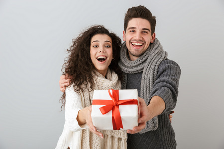 Image of beautiful man and woman rejoicing while standing with present box isolated over gray background Banco de Imagens