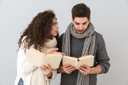 Image of smiling couple man and woman reading books together isolated over gray background